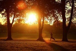 A woman runs through Victoria Park at sunrise in Leicester